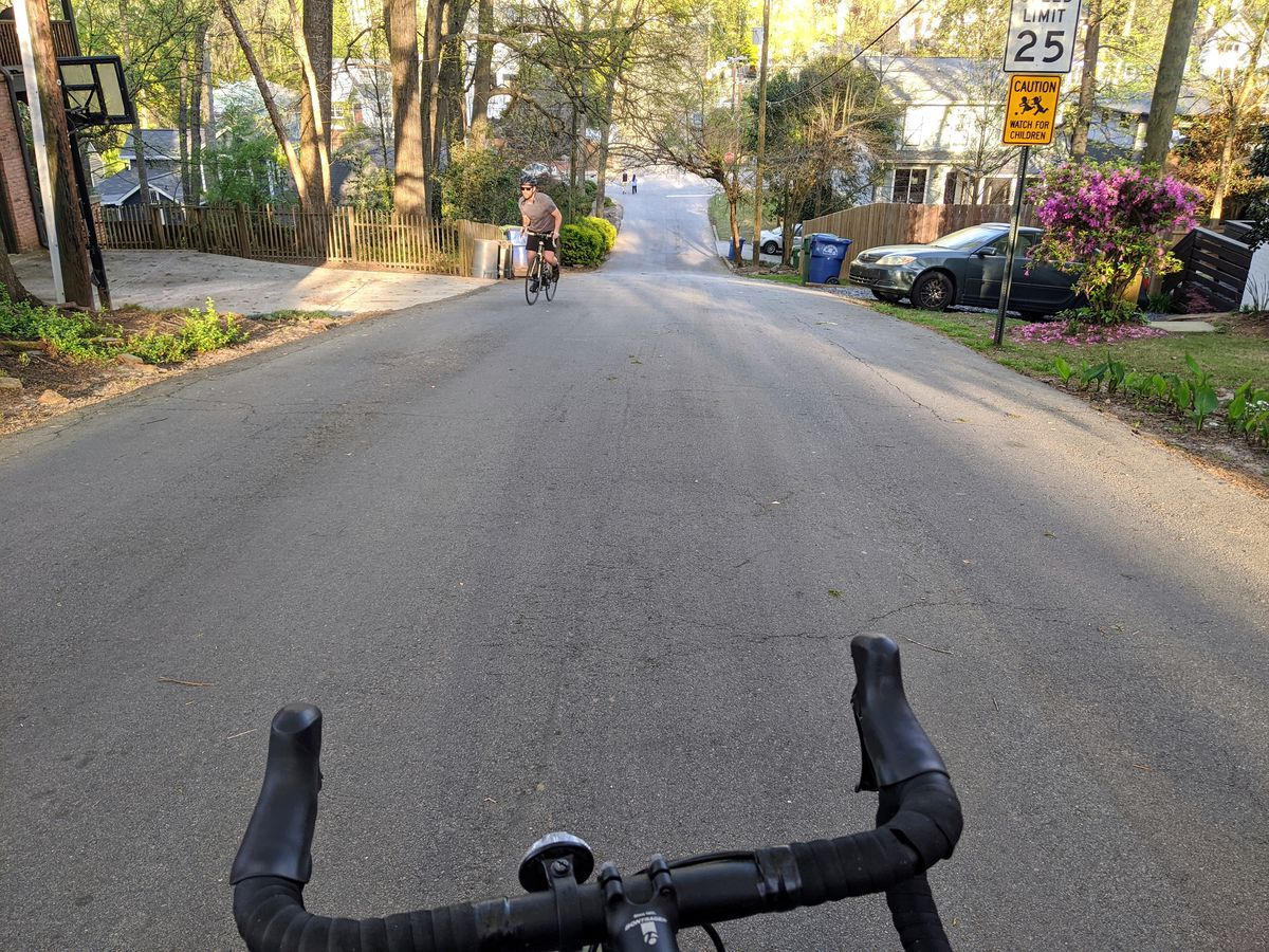 A street that slopes way down with a flowery bush at right and a man on a bike.