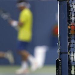 In this Sept. 2, 2012 photo, a TNT Gauge system is seen strapped on the anchor hook on the outside of a net post at Authur Ashe Stadium during third round of play at the 2012 US Open tennis tournament in New York. The gauge is a tool that measures the tension on a net cord and assists in efforts to provide as much consistency as possible on how balls bounce off the net. (AP Photo/Mike Groll)