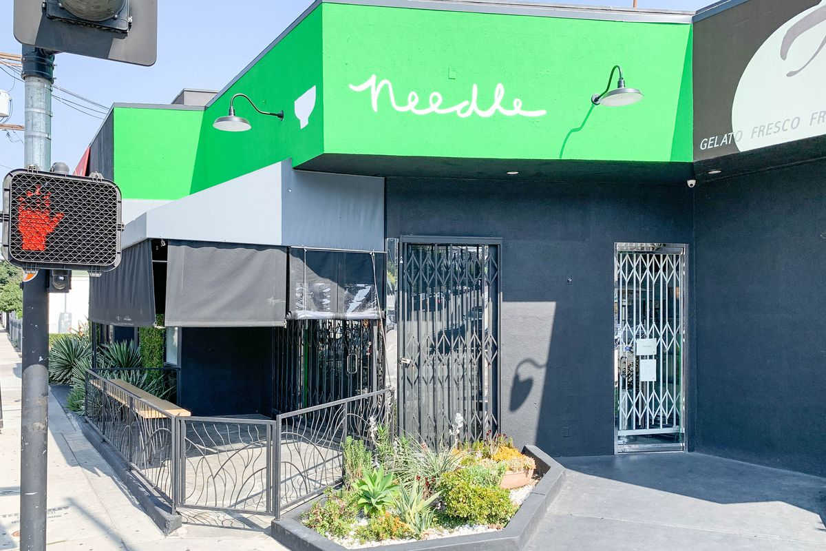 A closed restaurant storefront with bright green awning.