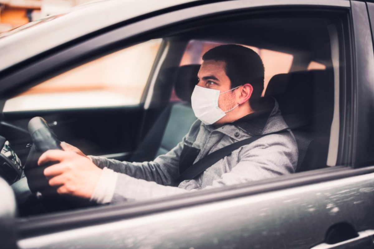 Man in a mask sits in a car with his hands on the wheel. Uber drivers can book a vaccine appointment through Walgreens' scheduling system using a code sent through the Uber app.
