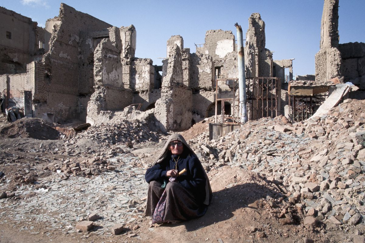 A woman sits before ruined buildings.