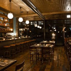 Nautical-looking metal meshing supports globe lighting over the bar