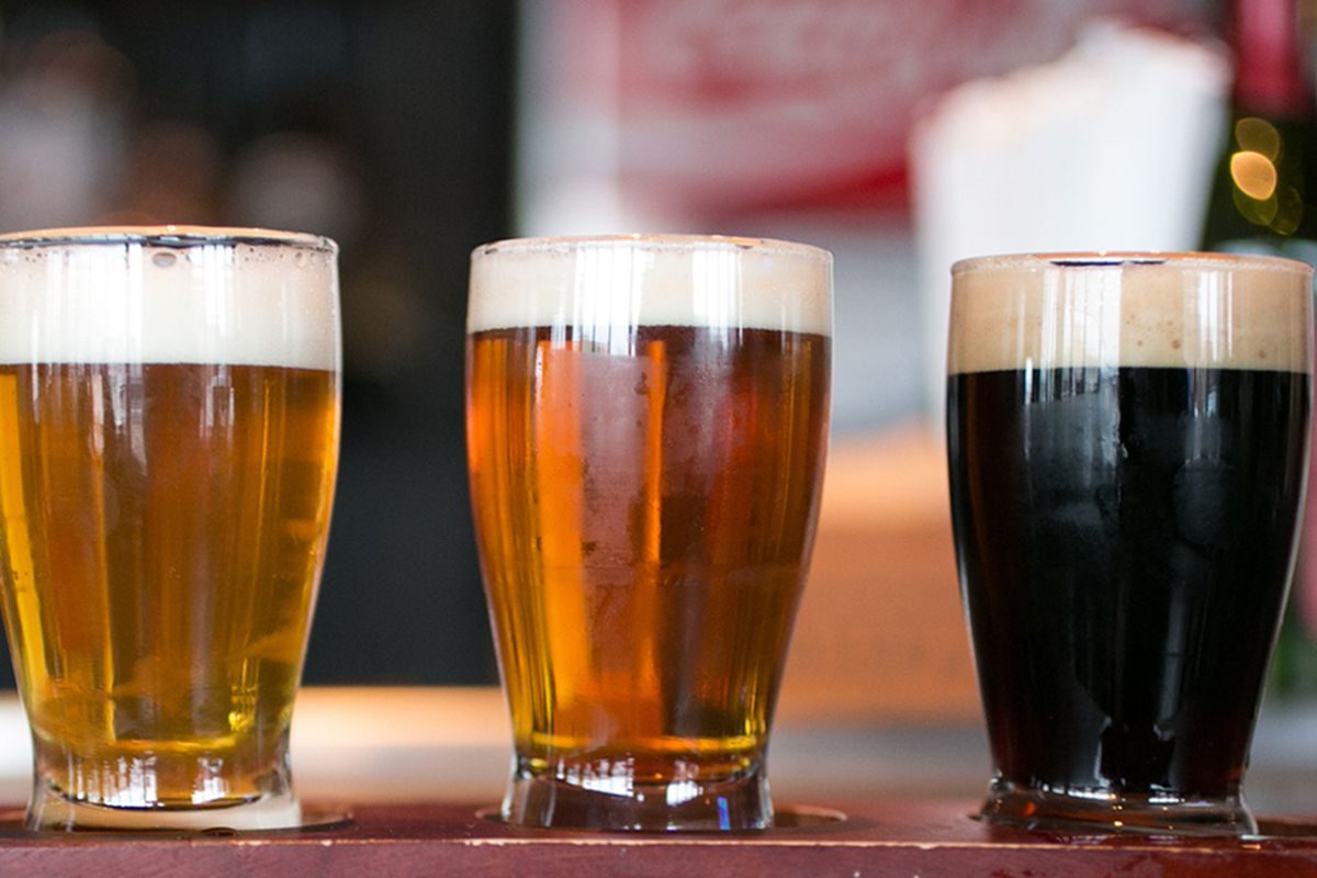 A row of four beers in tasting glasses shown from light to dark.