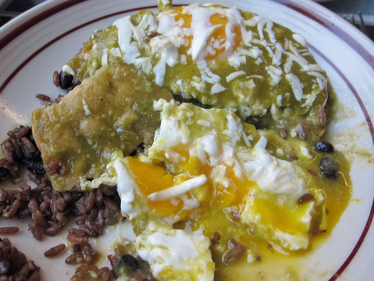Runny eggs exceedingly yellow and bright white broken up on tortillas.