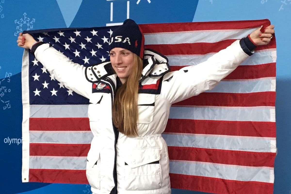 Luge athlete Erin Hamlin holds the American flag at a press conference in Pyeongchang, South Korea.