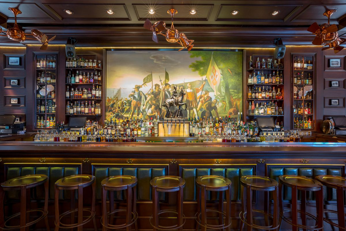 A dark-wooded bar with low stools in front and a painting of men with flags