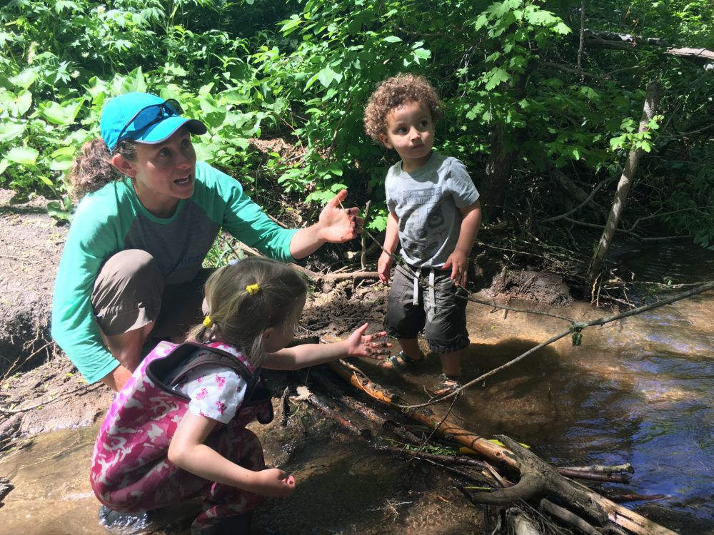 """Megan Patterson works with children to make a dam in a creek during a recent """"forest school"""" class."""