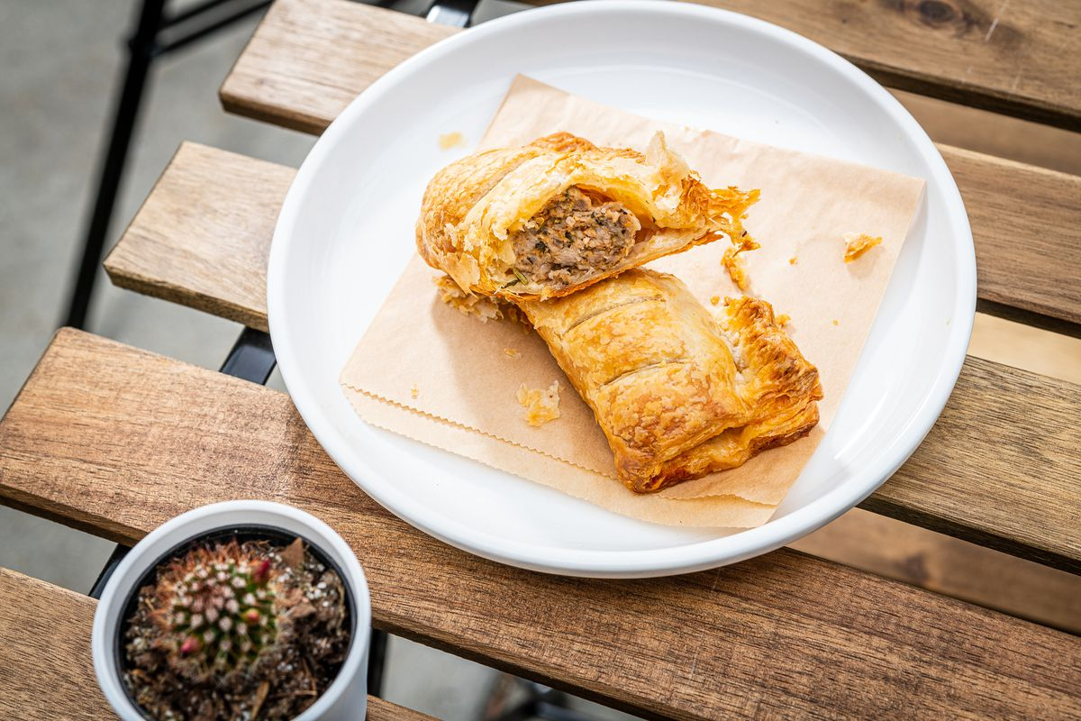 Little Food Studio's sausage roll pastry is cut in half to reveal a filling of pork, chicken, fennel, and sage.