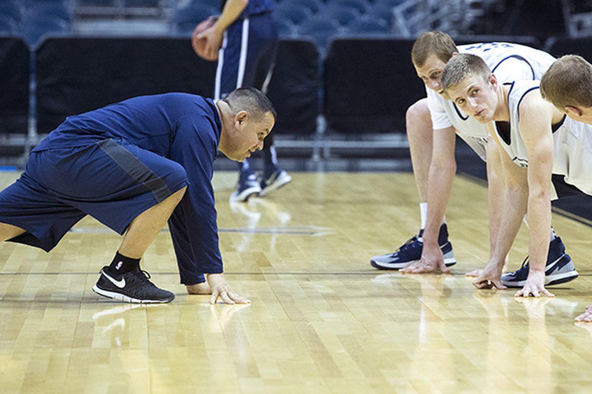 Bob Medina helps BYU basketball players stretch.
