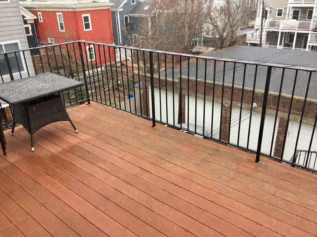 A small deck empty except for a small table.
