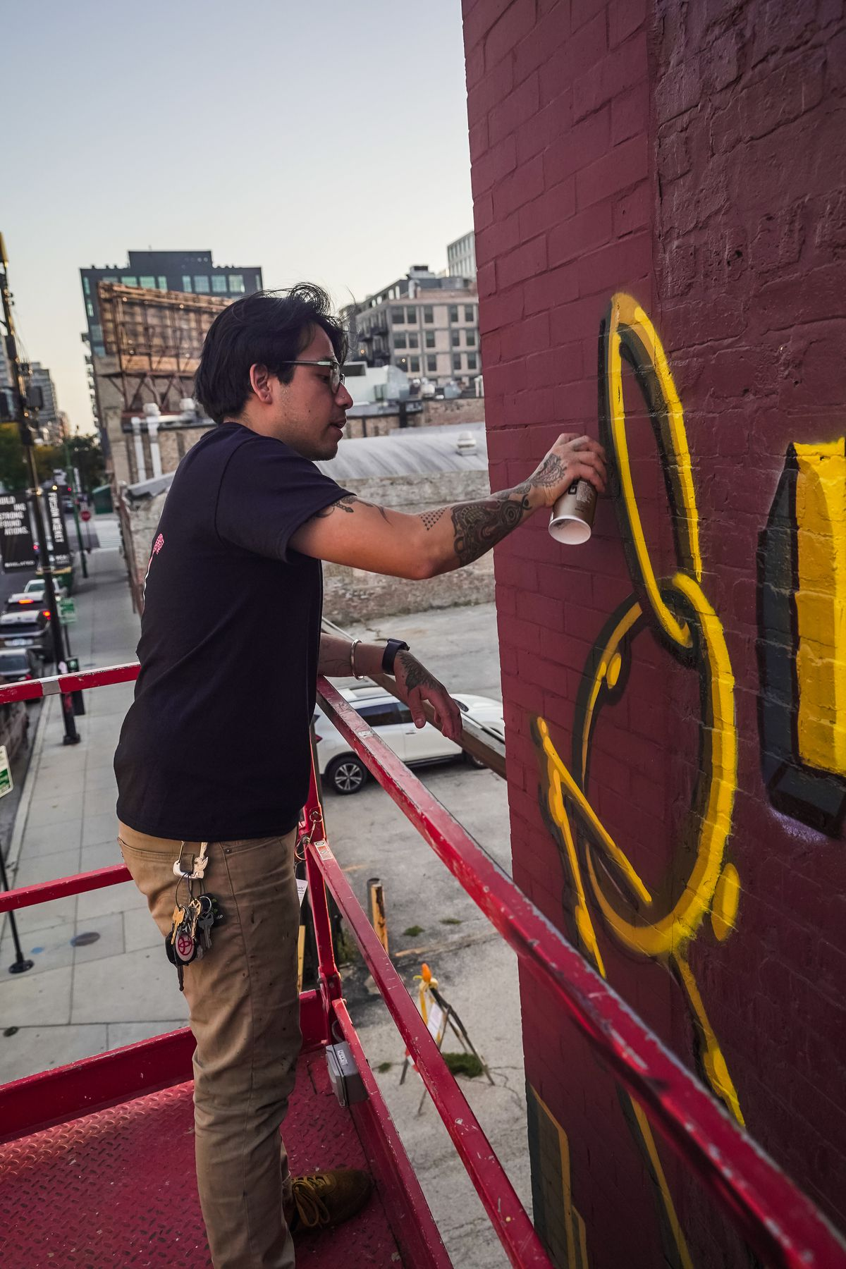 """Chris """"Killabunzz"""" Orta works on the gold chain detail in his section of the mural. Orta is one of five artists who worked on the mural, and works as a tattoo artist with fellow collaborator Jose """"Oinkz_"""" Quezada."""