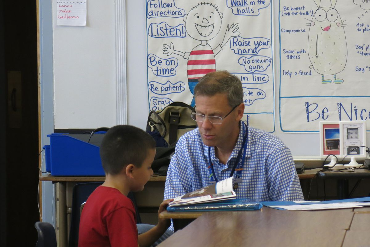 DPS superintendent Tom Boasberg reads with a student at an event called Power Lunch.