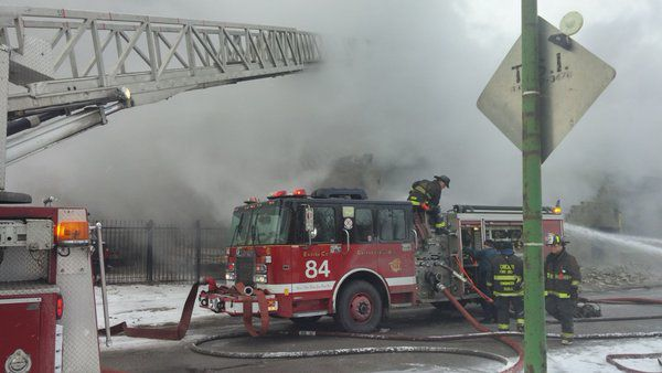 Smoke pours from a body shop in the 200 block of West 65th Street Tuesday morning.   Fire Media