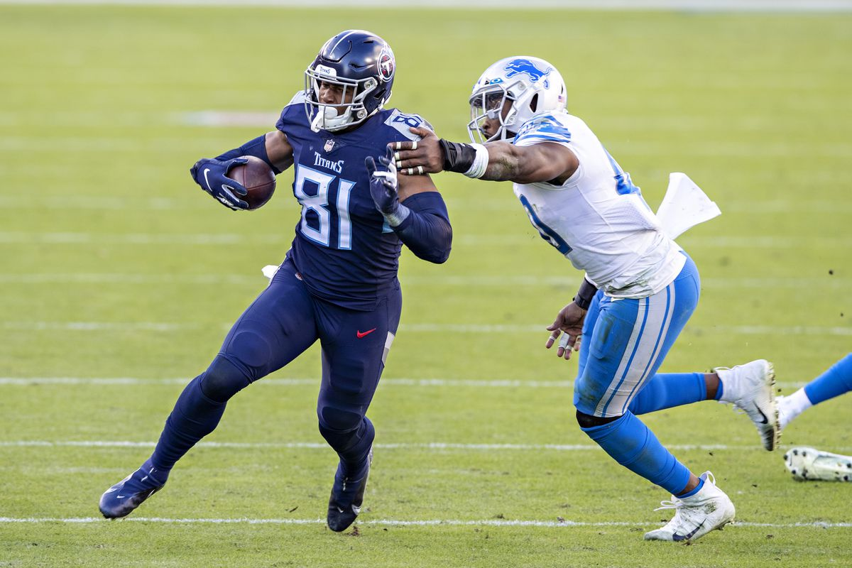 Tight end Jonnu Smith #81 of the Tennessee Titans runs the ball and is pushed out of bounds by linebacker Jarrad Davis #40 of the Detroit Lions at Nissan Stadium on December 20, 2020 in Nashville, Tennessee.