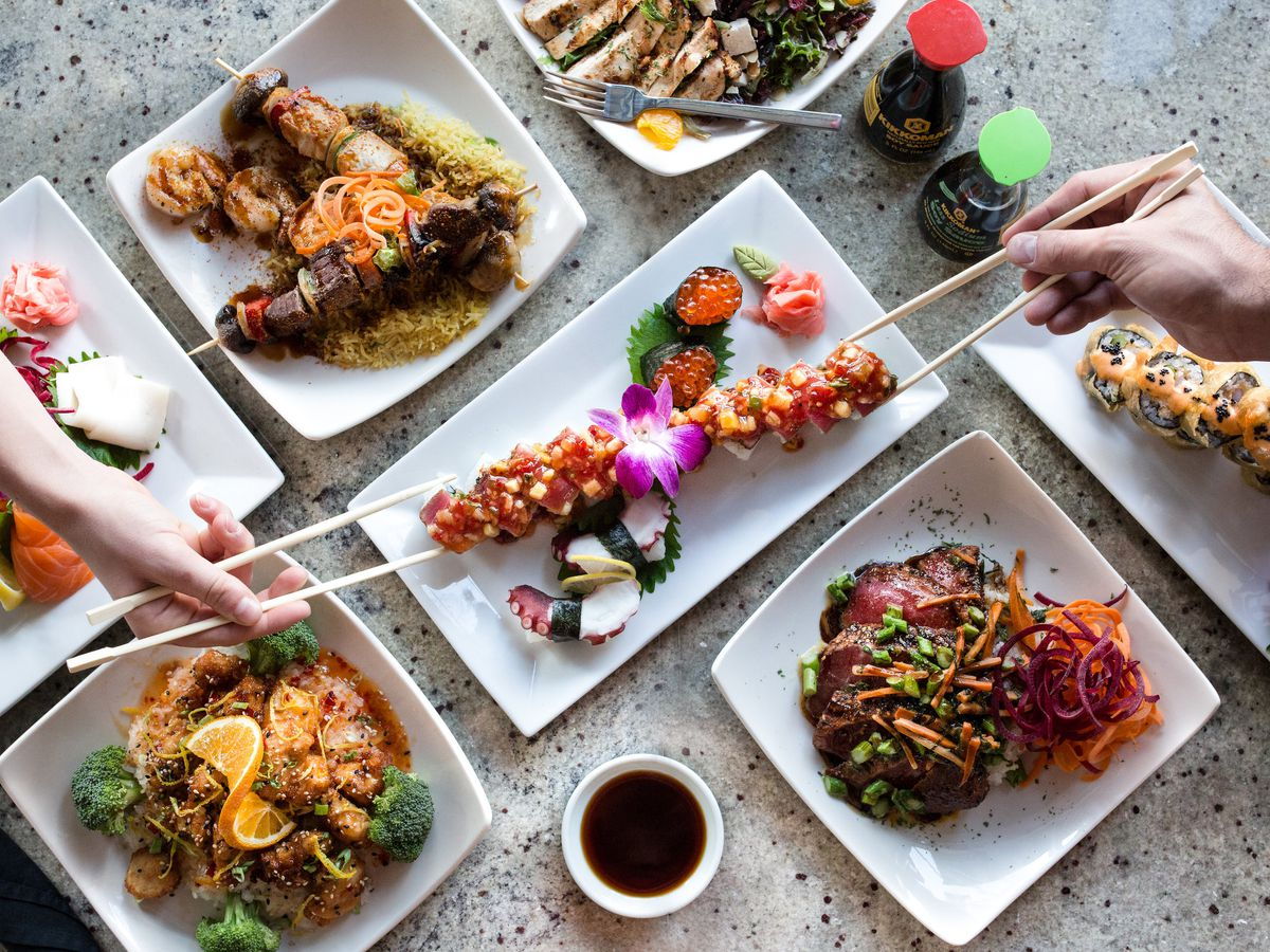 From above, two people reach in with chopsticks to sample a creative maki roll, surrounded on a table by other dishes like meat and seafood skewers, grilled tuna, and rice
