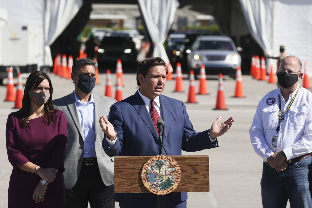 Florida Governor Ron DeSantis speaks at a lectern outside a drive-through Covid-19 vaccination site.