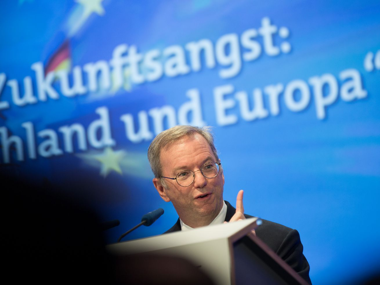 "Eric Schmidt speaks at a conference with the word ""Europa"" behind him."