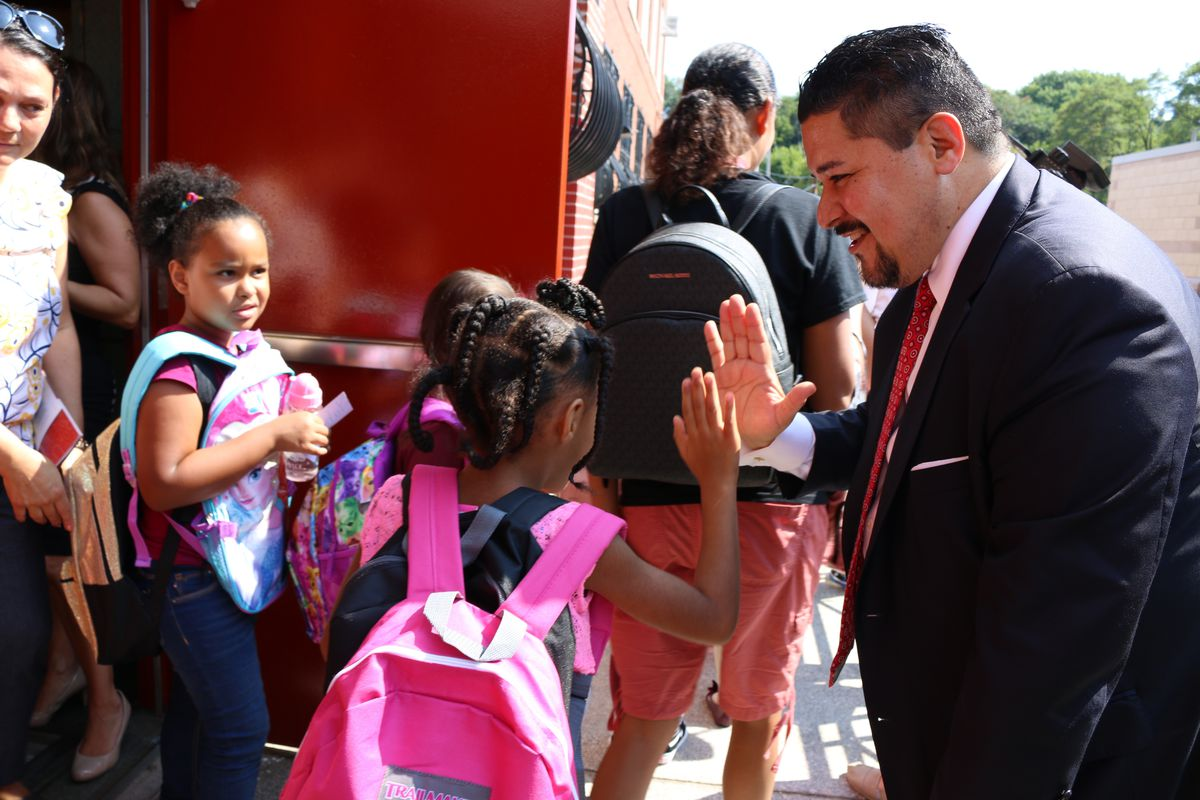 Schools Chancellor Richard Carranza high-fives students at P.S. 78 on Staten Island as they leave after the first day of the 2018-2019 school year.