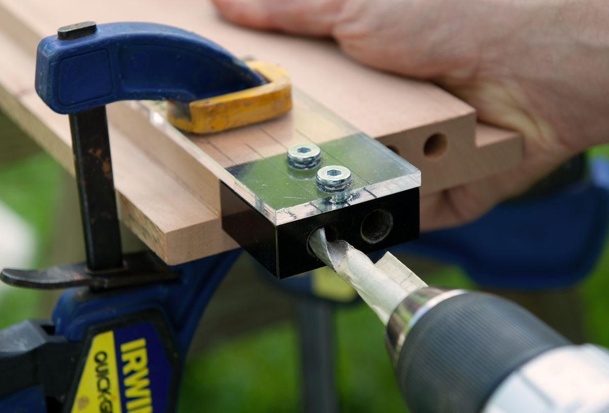 Man Drills Holes For Dowels Of Picnic Table