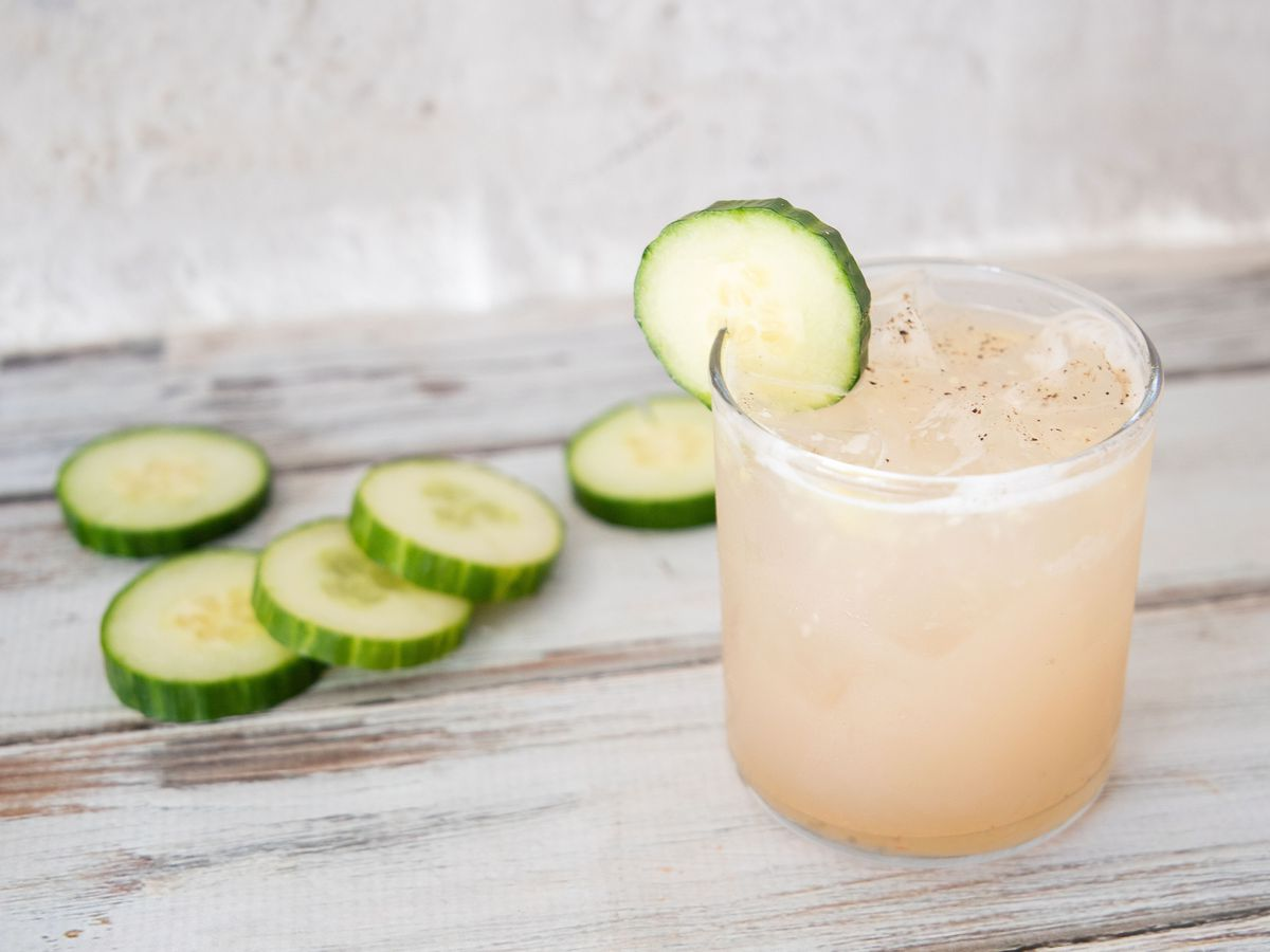 Cocktail with cucumber garnish next to slices of cucumbers.