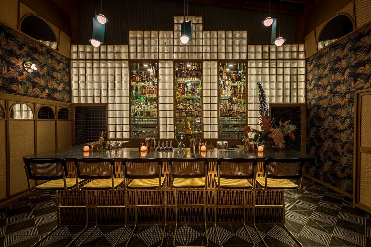 A glowing, moody cocktail bar with wicker chairs.