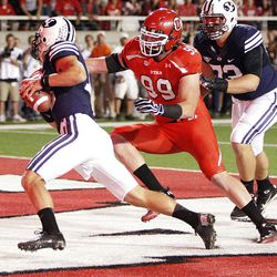 Brigham Young Cougars quarterback Riley Nelson (13) is sacked in the endzone by Utah Utes defensive end Joe Kruger (99) in Salt Lake City  Saturday, Sept. 15, 2012. Face masking was called on the play.