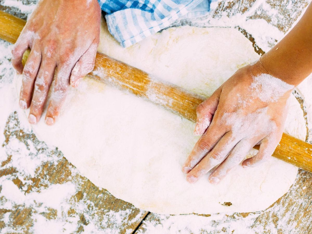 A baker rolls out dough on a floured counter