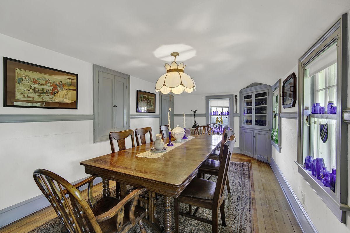 A dining area with a rectangular wooden table, hardwood floors, and base moldings.