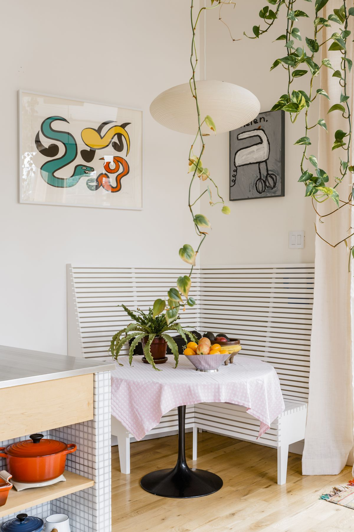The corner of a kitchen with built in sitting booth and a table that has a basket of fruit on it . There are plants hanging from planters on the ceiling and multiple framed works of art on the wall.