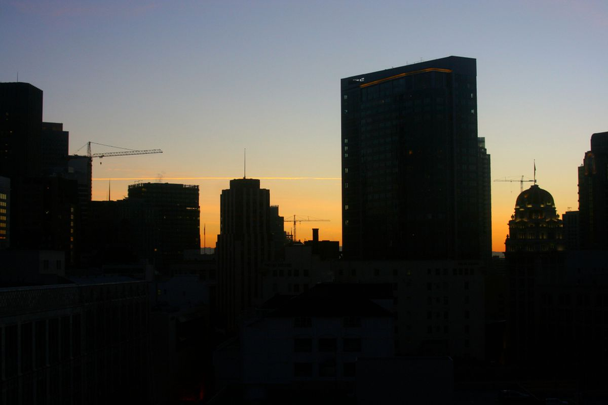 The San Francisco skyline at sunrise, in silhouette.