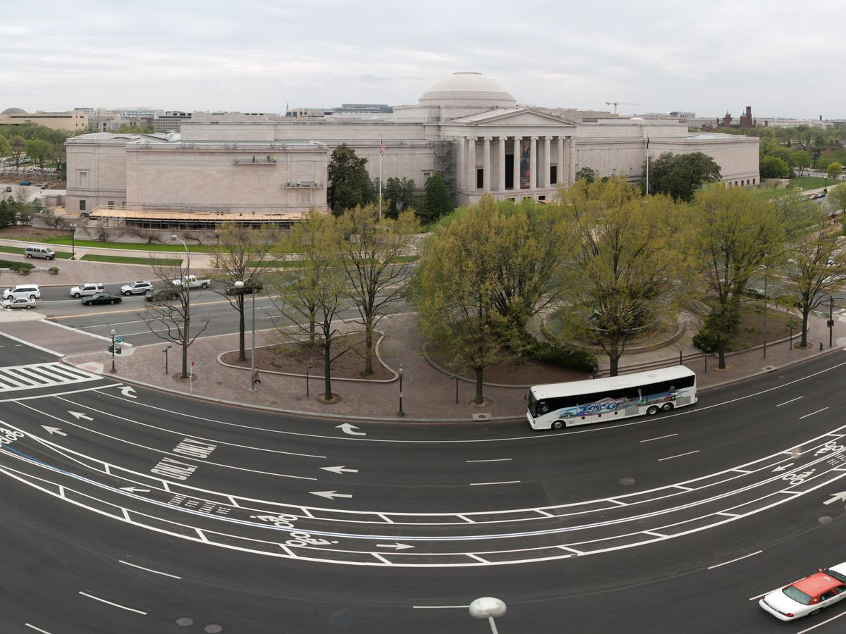 In the foreground is a street. In the distance is the Newseum in Washington D.C. The Newseum building is large and white and there are columns on the front facade.