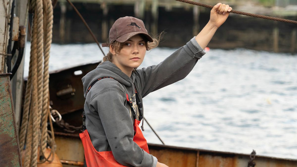 Emilia Jones as Ruby in CODA hanging on to a boat rope and wearing a sweatshirt and orange fisherman pants
