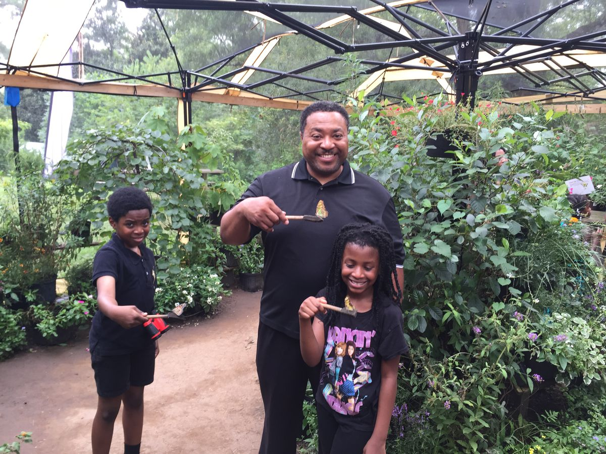 A man and two children stand in a greenhouse in the midst of many assorted varieties of plants.