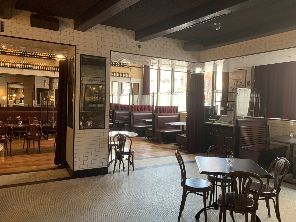 A French-inspired restaurant dining room, which features white subway tiled walls and dark maroon booths, has clear plastic dividers between booths and socially distanced tables