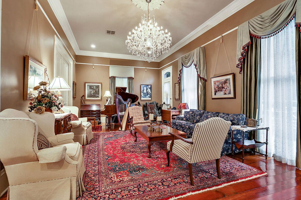 A formal parlor with a large crystal chandelier, antiques and musical instruments