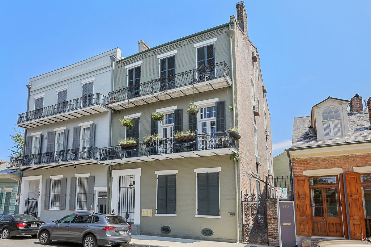 Two side-by-side three-story townhomes with iron balconies face a street with two parked cars.