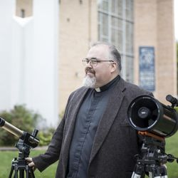 A portrait of Father James Kurzynski, an amateur astronomer and priest, with his telescopes at his church, St. Joseph Catholic Parish, in Menomonie, Wisconsin, on Aug. 9 2017.