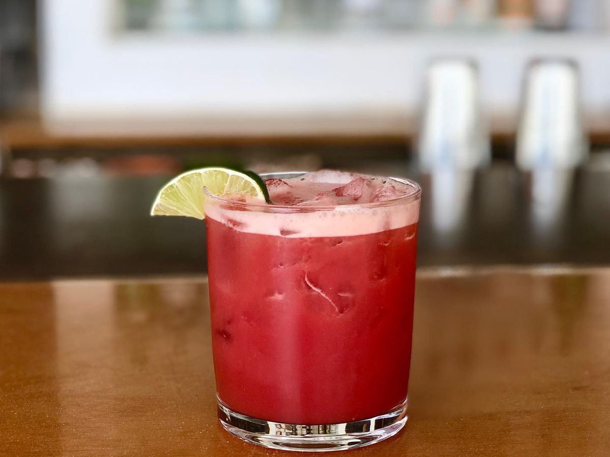 A bright red drink in a lowball glass garnished with a lime wedge on a wooden bar