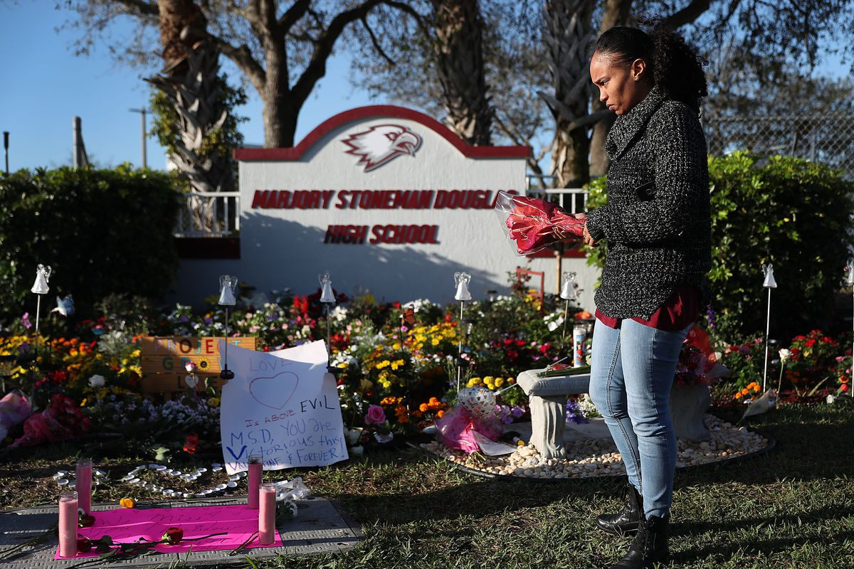 A woman lays flowers outside of Marjory Stoneman Douglas High School in Parkland, Florida in February 2019.