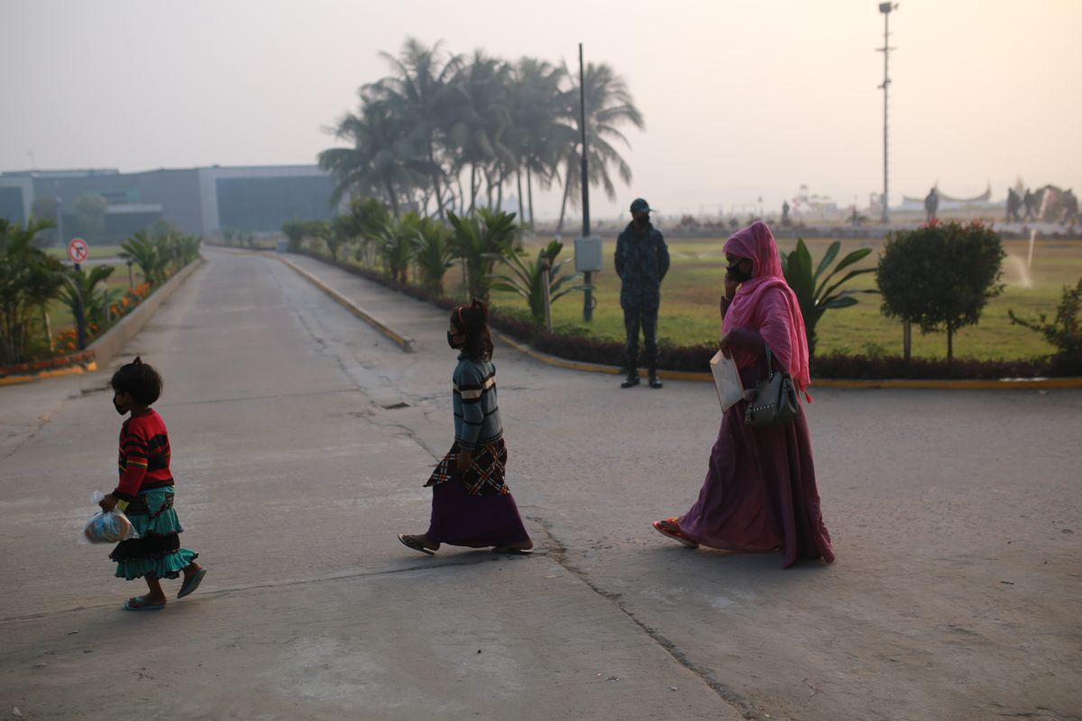 An adult and two children walk along a paved road.