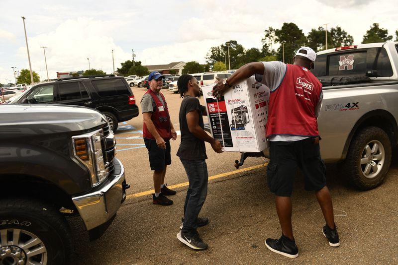 People load a generator onto a pick-up truck, ahead of Hurricane Ida.