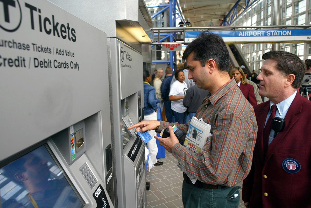 People lining up at a subway ticket dispenser.