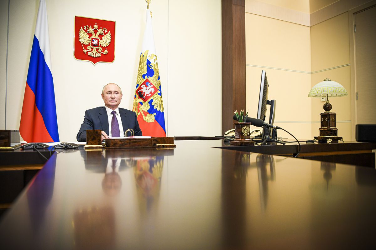 Russia's President Vladimir Putin sitting at a desk during a videoconference meeting.