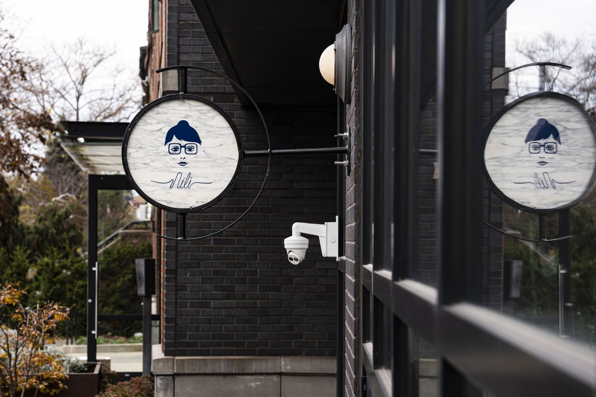 """A circular sign hangs outside of a coffee shop. A cartoon image of a person with a bob haircut and glasses appears on the sign, above the word """"Nili"""" in cursive."""