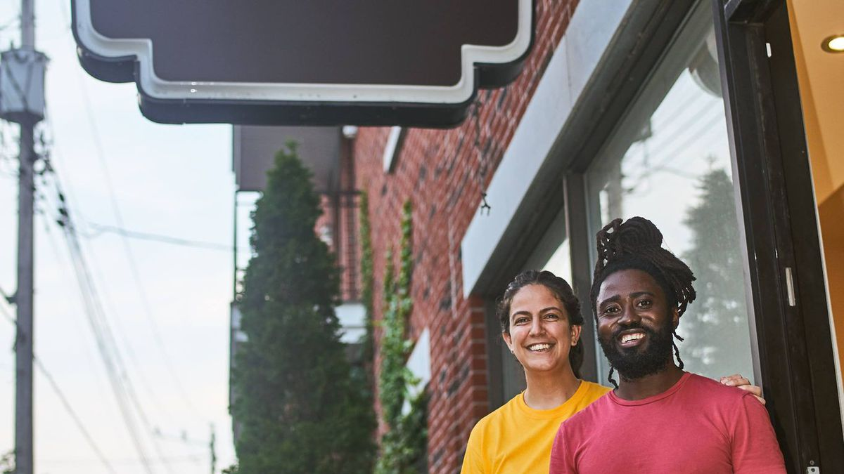 man and women in front of restaurant sign