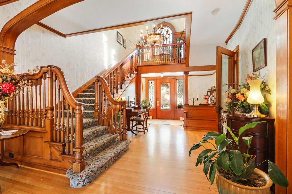 A foyer has a wooden staircase leading to the left, wood floors, and a chandelier hanging from the center.