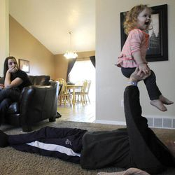Jeff Griffin plays with his 1-year-old daughter Katelyn as his wife Emily watches in their home in West Jordan on Thursday, Feb. 27, 2014.