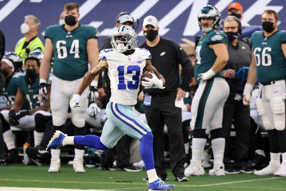 Michael Gallup #13 of the Dallas Cowboys runs down the sideline after a catch as the Philadelphia Eagles look on in the first half at AT&T Stadium on December 27, 2020 in Arlington, Texas.