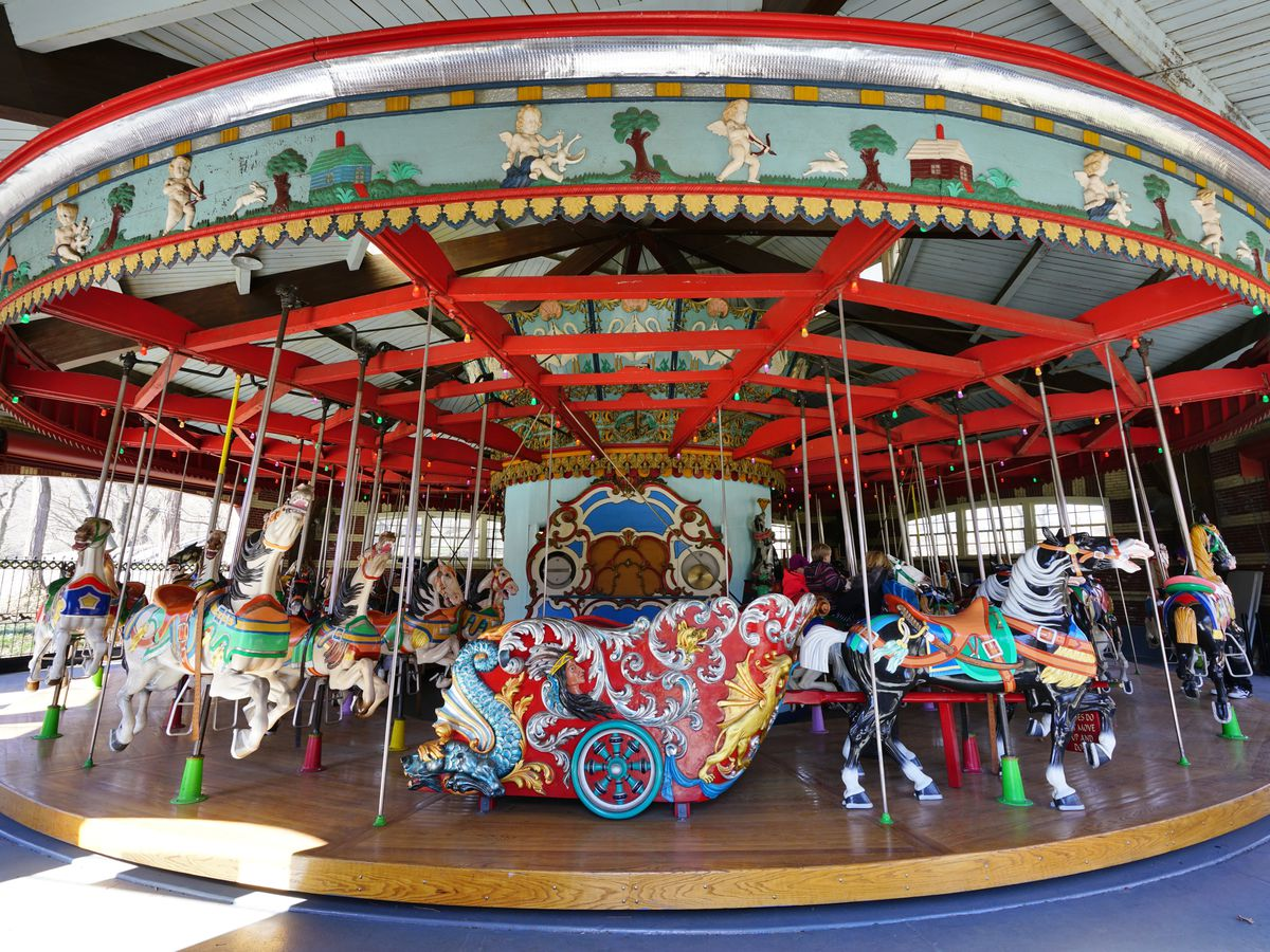 A historic merry-go-round that has red trim.
