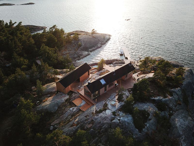 Aerial shot of two timber cabins on a rocky seaside landscape.